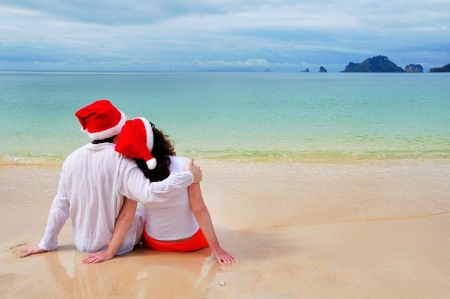 Christmas and New Year holiday concept, romantic couple in santa hats on tropical beach on vacation photo