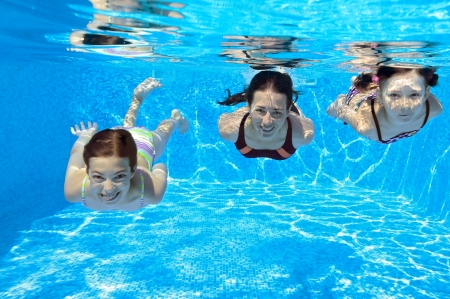 Happy family swim underwater in pool and having fun, mother and children on vacation photo