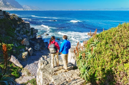 Happy couple looking at beautiful ocean view in Hermanus, romantic vacation in South Africa photo