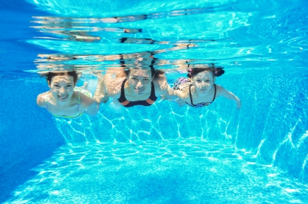 Šťastná rodina plavání pod vodou v bazénu a baví, matka a děti na dovolenou
