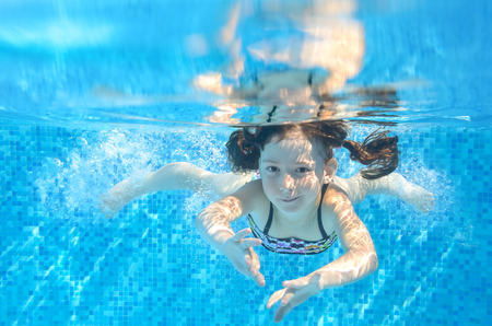 Bonne fille active nage sous-marine en piscine, belle piscine sain de l'enfant et de s'amuser en vacances d'été en famille, les enfants concept de sport Banque d'images