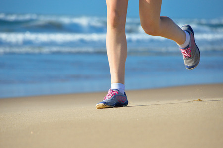 feet in sand: Woman runner legs in shoes on beach, running and sport concept