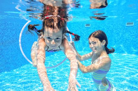 girl underwater: Gelukkige actieve kinderen zwemmen in het zwembad en spelen onderwater, meisjes duiken en plezier maken, kinderen op de zomervakantie, sport concept