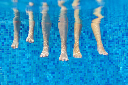 Funny underwater family legs in swimming pool, vacation and sport concept photo