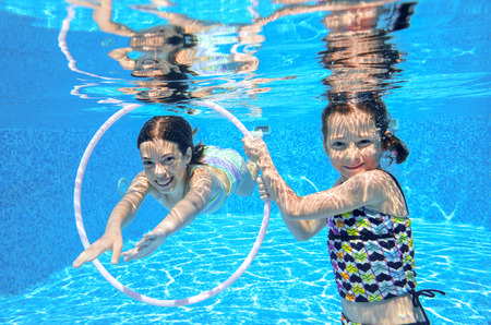 Happy active kids swim in pool and play underwater, girls diving and having fun, children on summer  vacation, sport concept 版權商用圖片