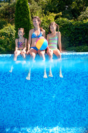 Happy family with kids having fun in swimming pool on vacation, underwater and above view photo