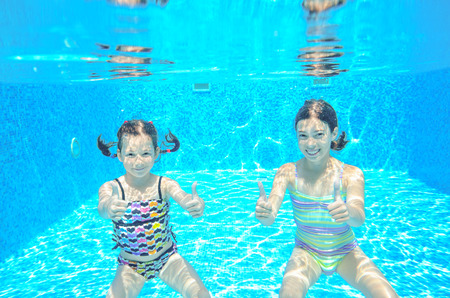 healthy family: Happy active kids swim in pool and play underwater, girls diving and having fun, children on summer  vacation, sport concept Stock Photo