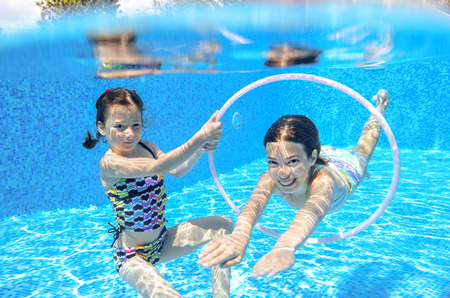 underwater woman: Happy active kids swim in pool and play underwater, girls diving and having fun, children on summer  vacation, sport concept Stock Photo