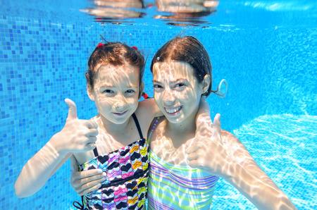 nadar: Ni�os activos felices nadan en la piscina y jugar bajo el agua, las ni�as de buceo y divertirse, los ni�os en las vacaciones de verano, concepto de deporte