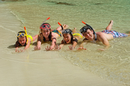 Happy family in snorkels on tropical beach having fun on sea vacation photo
