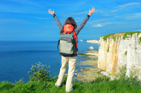 Woman hiking and looking at beautiful sea and rocks view, Alebaster coast, Normandy, France photo