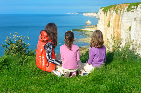 Mother and kids looking at beautiful sea view, family hiking on vacation in France, Etretat photo