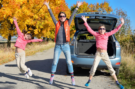 Car trip on autumn family vacation, happy mother and kids travel and have fun, car insurance concept Stock Photo