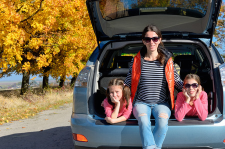 Car trip on autumn family vacation, happy mother and kids travel and have fun, car insurance concept photo