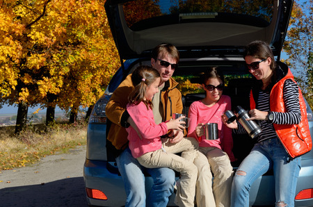 Car trip on autumn family vacation, happy parents and kids travel and have fun, car insurance concept photo