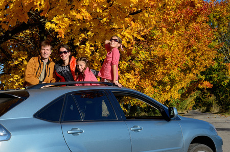 car concept: Car trip on autumn family vacation, happy parents and kids travel and have fun, car insurance concept