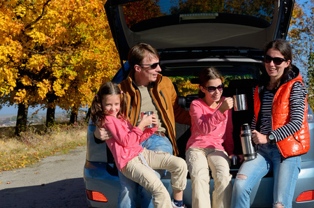 Путешествие на автомобиле по осень семейного отдыха, счастливые родители и дети путешествовать и веселиться, страхование автомобиля концепцию Фото со стока
