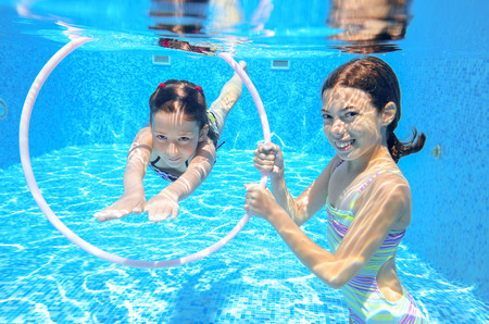Happy active kids play underwater in swimming pool photo