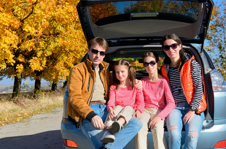 season: Car trip on autumn family vacation, happy parents and kids travel and have fun, car insurance concept