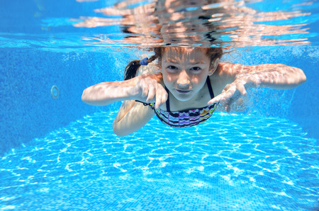 kids having fun: Happy active underwater child swims in pool, beautiful healthy girl swimming and having fun on family summer vacation, kids sport
