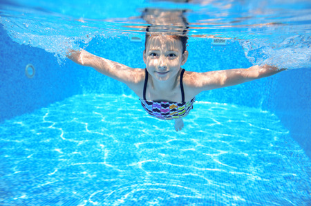 Happy active underwater child swims in pool, beautiful healthy girl swimming and having fun on family summer vacation, kids sport