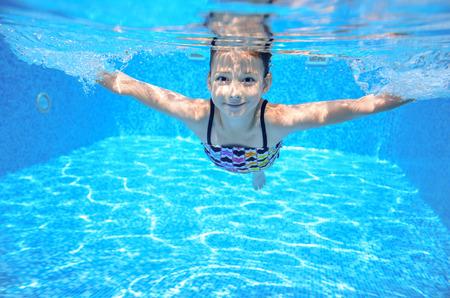nadar: Niño feliz bajo el agua activa nada en piscina, natación hermosa niña sana y divertirse en vacaciones de verano familia, niños deporte