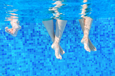 Funny underwater family legs in swimming pool, vacation and sport concept