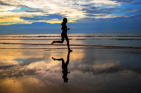 Silhouette of woman jogger running on sunset beach with reflection, fitness and healthy life concept photo