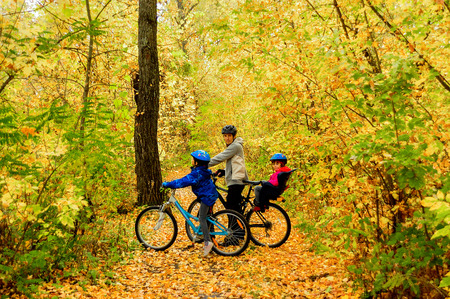 autumn colour: Family on bikes in autumn park, father and kids cycling, active family sport outdoors