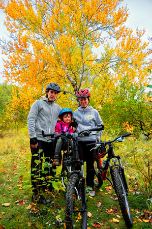 Family on bikes in autumn park, parents and kid cycling, active family sport outdoors, vertical image photo