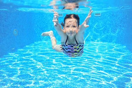 Kid swims in pool underwater, girl swimming, playing and having fun, children water sport Stock Photo