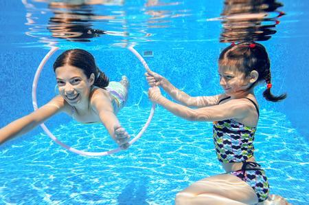 diving swimming pool: Kids swim in pool underwater, girls swimming, playing and having fun, children water sport