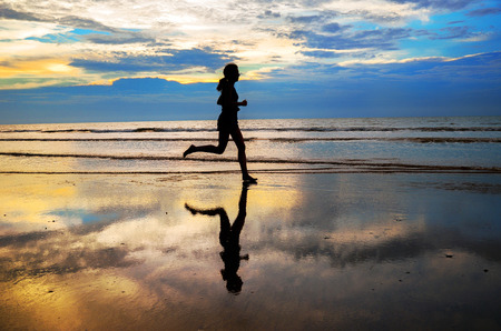 beach landscape: Silhouette of woman jogger running on sunset beach with reflection, fitness and healthy life concept