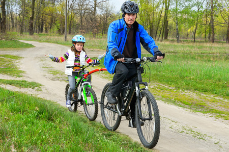Happy father and child on bikes, family cycling outdoors photo