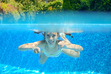 pool fun: Kid swims in pool underwater, girl swimming, playing and having fun, children water sport Stock Photo