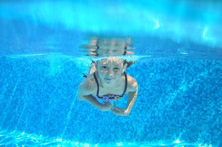 caucasian water drops: Kid swims in pool underwater, girl swimming, playing and having fun, children water sport Stock Photo
