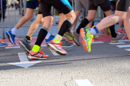 Marathon running race, people feet on road, sport, fitness and healthy lifestyle concept. Blurred motion in dynamics, focus on road