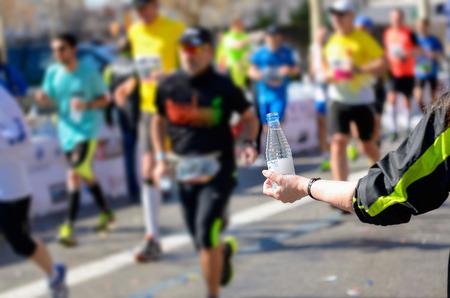 Marathon loopwedstrijd, lopers op weg, vrijwilliger water geven op verfrissing punt