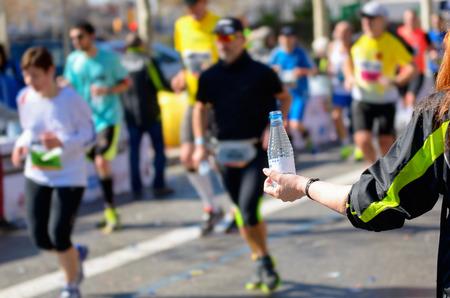 volunteer point: Marathon running race, runners on road, volunteer giving water on refreshment point