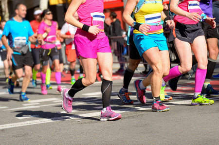Marathon running race, women runners feet on road, sport, fitness and healthy lifestyle concept