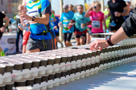 Marathon running race, runners on road, volunteer giving water and isotonic drinks on refreshment point Banque d'images