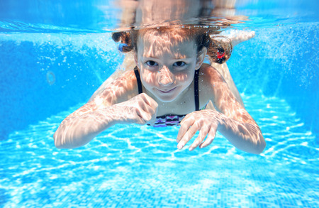 whitern: Happy girl swims in pool underwater, active kid swimming, playing and having fun, children water sport