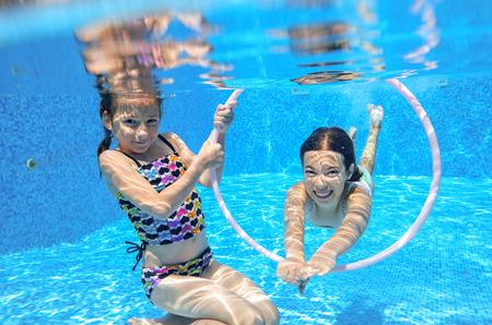 Happy children swim in pool underwater, girls swimming, playing and having fun, kids water sport