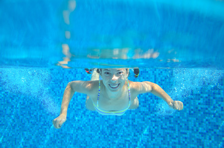 caucasian water drops: Happy girl swims in pool underwater, active kid swimming, playing and having fun, children water sport