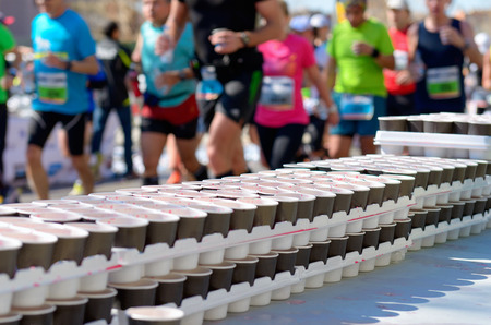 Marathon running race runners on road volunteer giving water and isotonic drinks on refreshment point