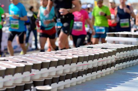 Marathon course à pied des coureurs sur route de bénévoles donnant de l'eau et des boissons isotoniques sur point de rafraîchissement