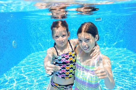 Happy children swim in pool underwater girls swimming playing and having fun kids water sport photo