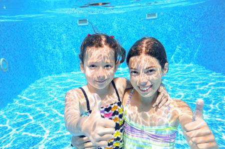 Happy children swim in pool underwater girls swimming playing and having fun kids water sport Stok Fotoğraf