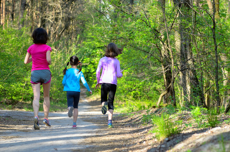 outdoor exercise: Family sport happy active mother and kids jogging outdoors running in forest