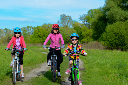 healthy path: Happy mother and kids on bikes cycling outdoors active family sport Stock Photo